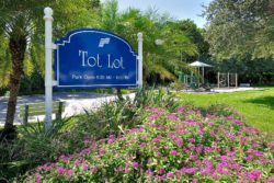 The Tot Lot sign and flower bed with play equipment in the background.