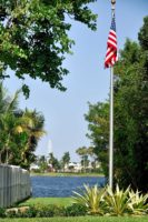 The flag pole at the Litoral Preserve, looking east with the lake and lighthouse in the background.